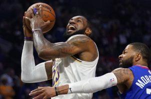 LeBron James (izq)de los Lakers anota una canasta ante Marcus Morris de losnClippers AP