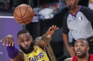 LeBron James (Izq.) de los Lakers, cede el balón ante la mirada de P.J. Tucker de los Rockets. Foto:EFE