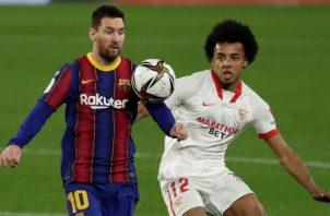 El defensa francés del Sevilla Jules Koundé (d) pelea un balón con el delantero argentino del Barcelona, Messi. Foto:EFE