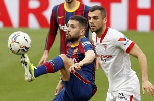 El defensa del Barcelona Jordi Alba (izq.) controla el balón ante el centrocampista del Sevilla Joan Jordán  Foto:EFE