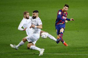 El delantero argentino del Barcelona, Leo Messi (der.) reamata el balón ante los defensores del Huesca. Foto:EFE