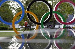 Una mujer con una máscara toma fotografías de un monumento de los Anillos Olímpicos cerca del Estadio Nacional, la sede principal de los Juegos Olímpicos de Tokio. Foto:EFE