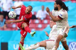 Martin Braithwaite de Dinamarca patea e balón ante la marca de dos jugadores de Bélgica. FOto:EFE