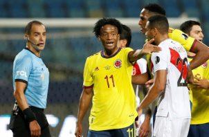 Juan Guillermo Cuadrado de Colombia discute una jugada durante el partido contra Perú. Foto:EFE