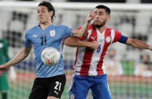 Edinson Cavani (izq.) de Uruguay disputa el balón con Junior Alonso de Paraguay. Foto:EFE