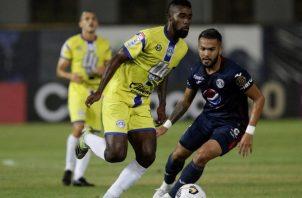 Everardo Rose de Universitario (izq.) disputa un balón contra Omar Elvir de Motagua. Foto:EFE