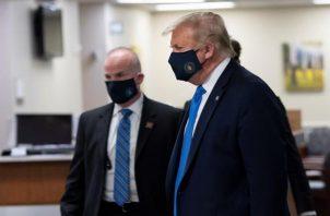 Cuando Trump fue visto este sábado con mascarilla, intentó ofrecer una imagen de fortaleza: iba rodeado de militares y miembros del servicio secreto que no se detuvieron ni un minuto ante las cámaras mientras el mandatario, al frente, dirigía el rumbo de la comitiva. FOTO/EFE