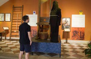 """Un hombre observa una guillotina que forma parte de la exposición """"Inquisición. EFE"""