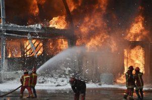 Un helicóptero de la armada lanza agua al fuego en el puerto de Beirut (Líbano). Fotos:EFE.