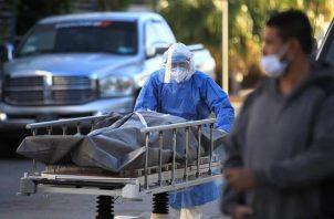 Un paramédico traslada un cuerpo de una persona fallecida por la COVID-19