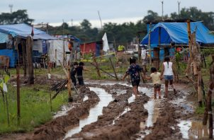 """Niños recorren un camino lodoso en el terreno """"Victoriano Lorenzo"""", en el sector de la 24 de Diciembre."""