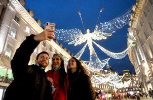 Compradores posan para una fotografía mientras se dirigen a Regents Street en Londres, donde se ha dado un aumento de contagios de COVID-19. Foto: EFE