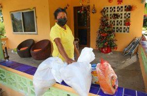 Las bolsas con comida se reparten en las áreas rurales.