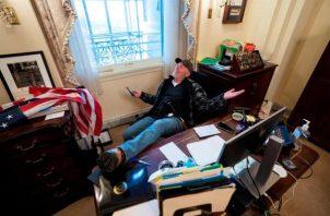 Un seguidor de Donald Trump se sienta en el escritorio de la presidenta de la Cámara Baja.