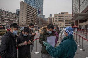 Personas llegan hoy al hospital en Beijing, China,  para hacerse la prueba de la covid-19. Foto: EFE