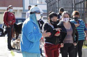 Personal médico organiza una fila de personas que se van tomar pruebas de covid-19