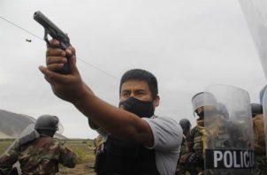 Un miembro de la Policía mientras apunta su arma a manifestantes durante una protesta de trabajadores agroindustriales