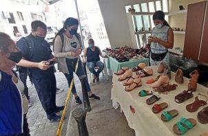 Varias personas observan algunos modelos en un puesto de venta de sandalias hoy, en La Habana