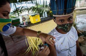 Una trabajadora del Distrito Sanitario Especial Indígena (DSEI) de Manaos vacuna a la indígena Ruan Viana, de 18 años. EFE