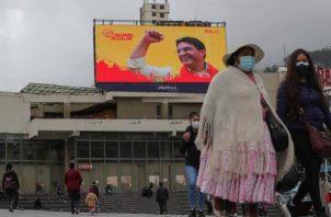 Varias personas frente a una pantalla gigante de publicidad electoral, el jueves 4 de febrero de 2021, en La Paz