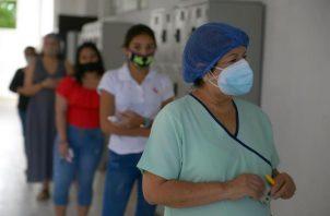 Mujeres esperan en fila para votar hoy, en un centro electoral en Guayaquil
