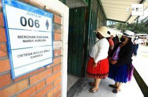 Varias personas esperan para votar en las elecciones generales en Cuenta (Ecuador).