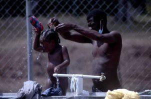 Un padre migrante baña a su hijo en el albergue de San Vicente, provincia de Darién. Víctor Arosemena