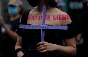 Una mujer marcha con una cruz durante una manifestación con motivo del Día Internacional de la Eliminación de la Violencia contra las Mujeres. EFE
