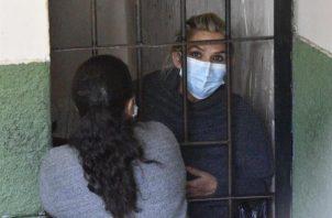 La expresidenta interina de Bolivia Jeanine Áñez se asoma desde las celdas de la Fuerza Especial de Lucha Contra el Crimen (Felcc). EFE