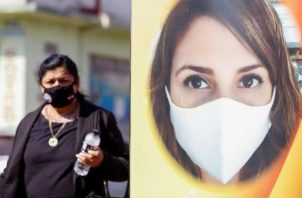 Fotografía que muestra una mujer mientras pasa al lado de un cartel hoy en la zona del mercado 4 de Asunción (Paraguay).