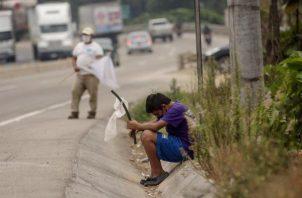 Un niño ondea una bandera blanca en la carretera pidiendo ayuda por hambre debido a la crisis económica provocada por el coronavirus.