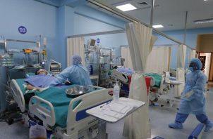 Trabajadores de la salud atienden nuevos pacientes covid-19 dentro de la Unidad de Cuidados Intensivos del Hospital Alberto Sabogal en el Callao (Perú).