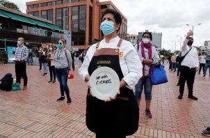 Una mujer sostiene un plato durante una protesta del gremio Asobares, hoy en Bogotá (Colombia).