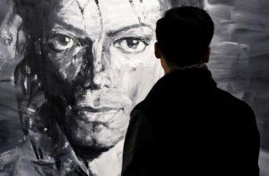 Un visitante observa las obras del artista chino Yan Pei-Ming de Michael Jackson. EFE