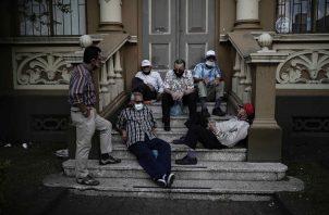Varios hombres, algunos sin el uso correcto del tapabocas, conversan en las escalinatas de un edificio en una calle de San José, Costa Rica. Foto: EFE