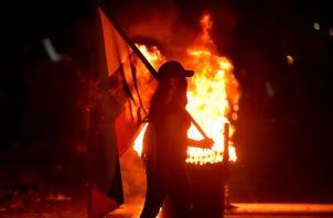 Fotografía del 3 de mayo de 2021 que muestra a un grupo de manifestantes que incendian llantas mientras bloquean vías durante las protestas en Cali (Colombia). Foto: EFE