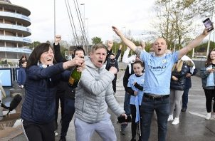Los seguidores del Manchester City celebran que su club ganó el título de la Premier League, después de que el Manchester United perdiera ante el Leicester. Foto: EFE
