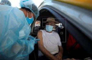 Las vacunas de AstraZeneca se colocan en auto exprés. Foto: EFE