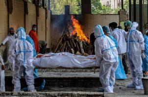 Las personas realizan los últimos ritos de una víctima de covid-19 en un campo de cremación en Nueva Delhi, India. Foto: EFE
