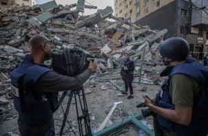 El equipo de televisión palestino trabaja junto a los escombros de su oficina destruida, la torre Al-Jalaa, que alberga apartamentos y varios medios de comunicación en la ciudad de Gaza. Foto: EFE