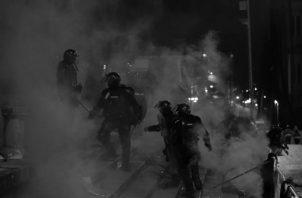 El choque entre antimotines y civiles parece haberse convertido ya en un cuadro que hemos visto incontables veces. Una escena repetida de una obra que ya conocemos. Foto: EFE.