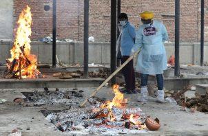 Voluntarios desinfectan durante un funeral masivo de víctimas de covid-19 en un crematorio en Nueva Delhi, India. Foto: EFE