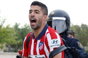 Luis Suárez es reducido por un policía tras celebrar con la afición. Foto: EFE