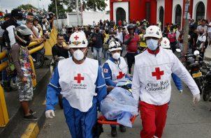 Miembros de la Cruz Roja Colombiana levantan el cuerpo sin vida de un hombre hoy, durante las manifestaciones en el sector La Luna, en Cali (Colombia).