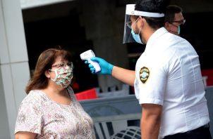 Un agente de seguridad de Universal Studios mide la temperatura a una señora que ingresa a dicho parque temático en Orlando, Florida (EE.UU).
