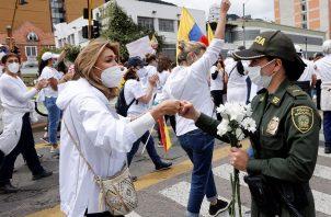 """Una mujer y una policía se saludan hoy en Bogotá, Colombia, durante una marcha que rechaza y pide el fin del """"Paro Nacional"""" y la violencia. Foto: EFE"""
