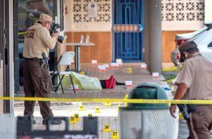 Un oficial de policía fotografía el cuerpo de una de las víctimas del tiroteo registrado en la entrada del salón de banquetes Billiards en Miami Gardens, Florida, Estados Unidos, este 30 de mayo.