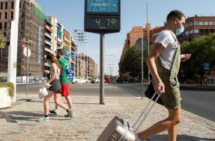Varias personas pasan ante el termómetro próximo a la estación de autobuses de Plaza de Armas de Sevilla en un día en que las temperaturas máximas superan los 40 grados. Foto:EFE