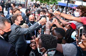 Emmanuel Macron (izq.) saluda, como es su costumbre, a miembros de una multitud durante su visita a Valence, Francia. Foto: EFE