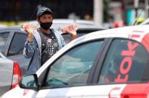Un adolescente vende bebidas entre las filas de vehículos en Ciudad de México Foto: EFE